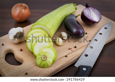 Zucchini, garlic, onion and eggplant on a board in the kitchen - stock photo