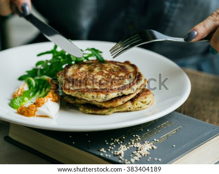 Zucchini pancakes with quinoa, greens and creamy sauces, female hand holding a fork and a knife - stock photo