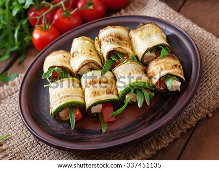 Zucchini rolls with cheese, bell peppers and arugula - stock photo