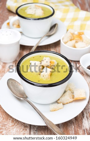 zucchini soup with croutons on the wooden table - stock photo
