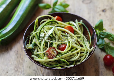 Zucchini spaghetti with rough basil and walnut pesto and cherry tomatoes