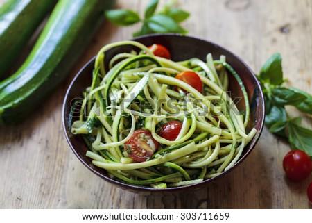 Zucchini spaghetti with rough basil and walnut pesto and cherry tomatoes - stock photo