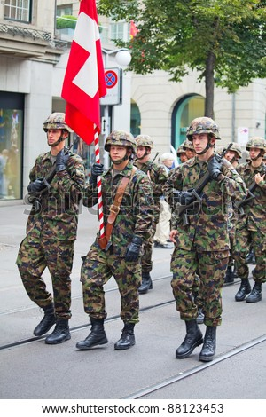 ZURICH - AUGUST 1: Infantery division of Swiss army marching in the Swiss National Day parade on August 1, 2009 in Zurich, Switzerland. - stock photo