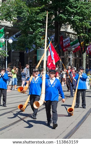 ZURICH - AUGUST 1: Representatives of canton Glarus with traditional alphorns participating in the Swiss National Day parade on August 1, 2009 in Zurich, Switzerland. - stock photo