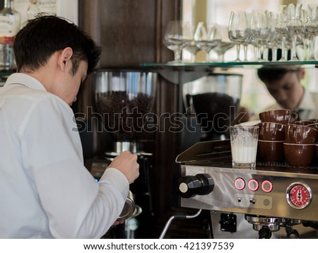 ZURICH, SWITZERLAND - APRIL 25, 2016: Young male barista making a cappuccino in a cafe in the old city of Zurich