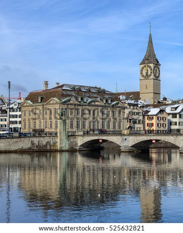 Zurich, Switzerland - 18 January, 2016: Muensterbruecke bridge over the Limmat river, tower of the St. Peter church and old town buildings in the background. Zurich is the largest city in Switzerland.