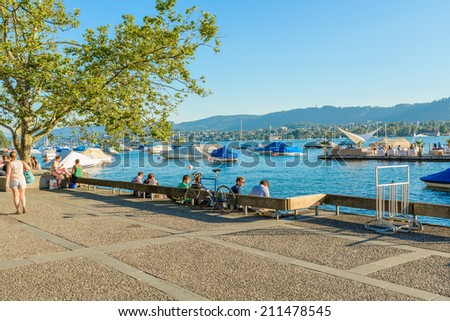 Zurich, Switzerland - 17 July, 2014: local people relax with the swans on Lake Zurich. Zurich is the largest city in Switzerland and the capital of the canton of Zurich. - stock photo