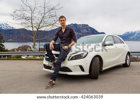 Zurich, Switzerland. March 10, 2016. Beautiful white Mercedes parked by the side of the street with a young man sitting on it. - stock photo