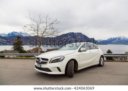 Zurich, Switzerland. March 10, 2016. Beautiful white Mercedes parked by the side of the street with the mountains on the background.