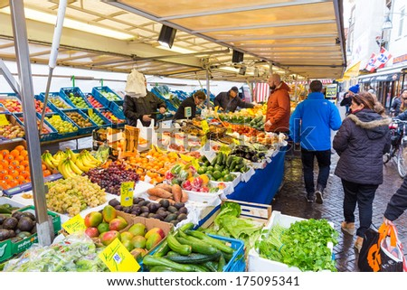 ZWOLLE, THE NETHERLANDS - FEBRUARY 1, 2014: Unidentified peope buying groceries at the street market in Zwolle. In the Netherlands there are 18,000 merchants realizing a 2.6 billion turn over.