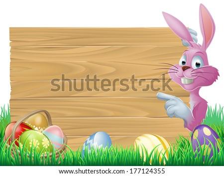 A cartoon pink Easter bunny rabbit peeping round a sign in green spring field full of chocolate decorated eggs