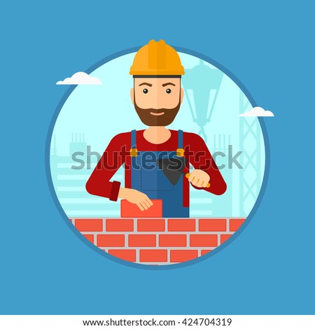 A hipster bricklayer in uniform and hard hat. Bricklayer working with a spatula and a brick in hands on construction site. Vector flat design illustration in the circle isolated on background. - stock vector