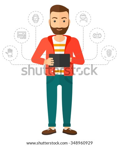 A hipster man with the beard standing with a tablet and some icons connected to the laptop vector flat design illustration isolated on white background. Vertical layout. - stock vector