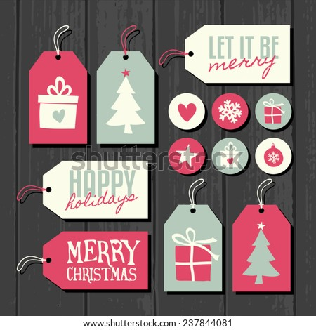 A set of Christmas gift and sale tags, round stickers and labels on a gray wooden background. - stock vector
