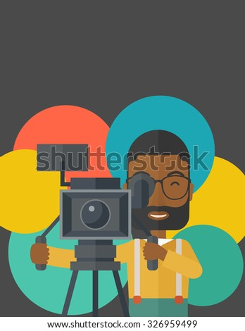 An African American cameraman with beard and glasses looking through movie camera on a tripod vector flat design illustration. Vertical layout with a text space. - stock vector