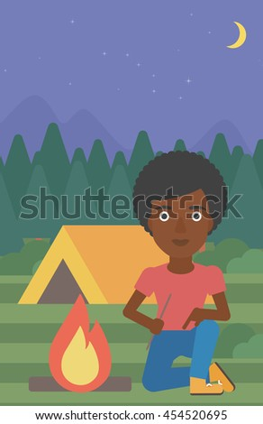 An african-american woman kindling campfire on the background of camping site with tent. Tourist relaxing near campfire. Woman sitting near campfire. Vector flat design illustration. Vertical layout. - stock vector