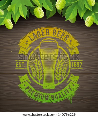 Beer emblem painted on wooden surface and ripe hops and leaves - vector illustration - stock vector