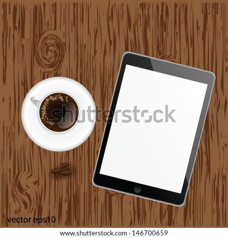 Black digital tablet on wood with a cup of coffee