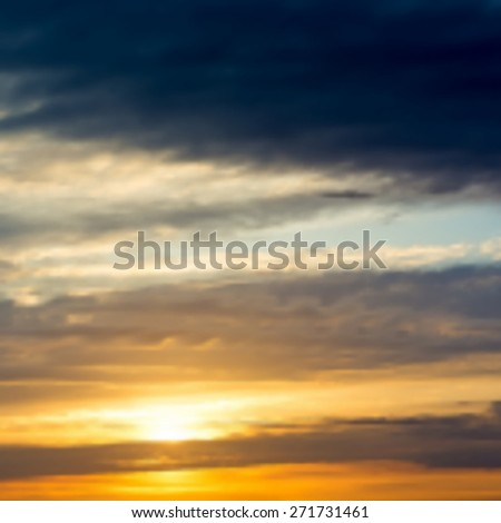 Blurred background with sunset / sunrise in the sky with dramatic clouds.