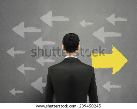 businessman faces left or right choices over grey - stock vector