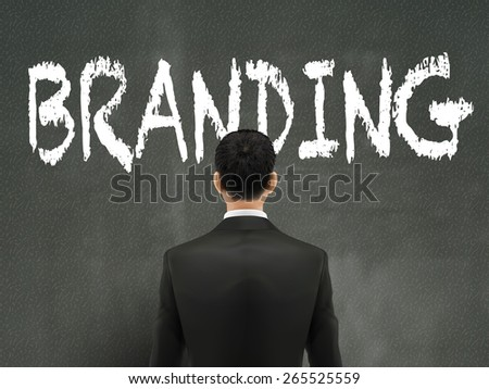 businessman looking at branding word on wall - stock vector