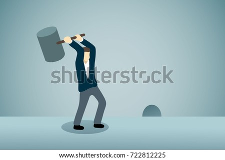 Businessman waiting for breaking something out from rat hole with hammer.