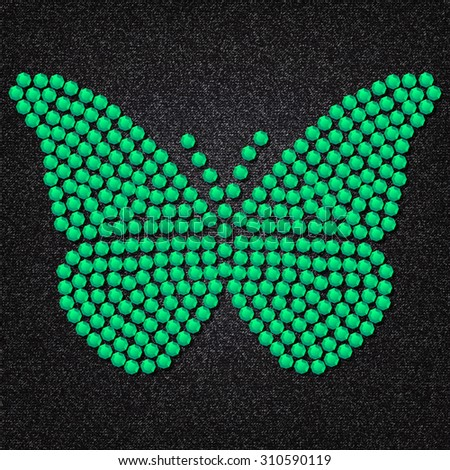 Butterfly built of green gems on a background of black and gray fabric.