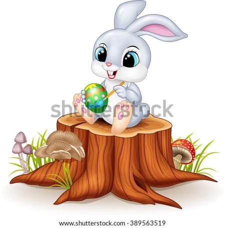 Cartoon Easter Bunny painting an egg on tree stump - stock vector