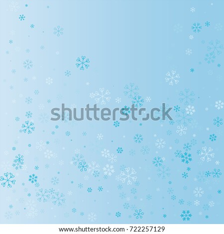 Christmas background with random scatter explosion of falling blue snowflakes on a blue background.