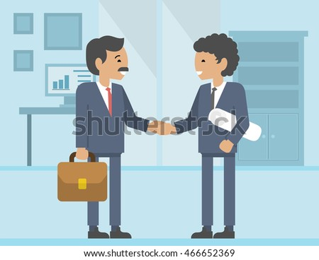 Close-up of two business people shaking hands while sitting at the working place