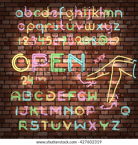 Color neon font set. Glowing typeface on the old red brick wall background. Uppercase and small case letters, number digits an symbols