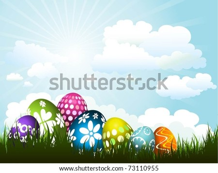 Colourful Easter eggs in grass against a sunny blue sky
