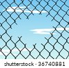 Cut wire fence with blue sky and clouds background. - stock photo