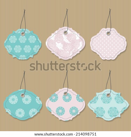Cute textile label tags in aquamarine and pale pink colors on cardboard background.