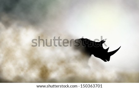 Editable vector illustration of a charging rhinoceros and dust cloud made using a gradient mesh - stock vector
