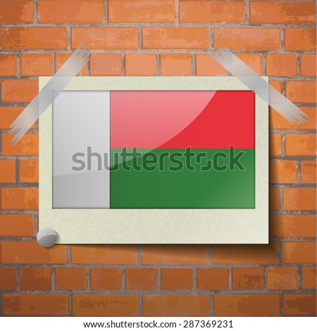 Flags of Madagascar scotch taped to a red brick wall. Vector - stock vector