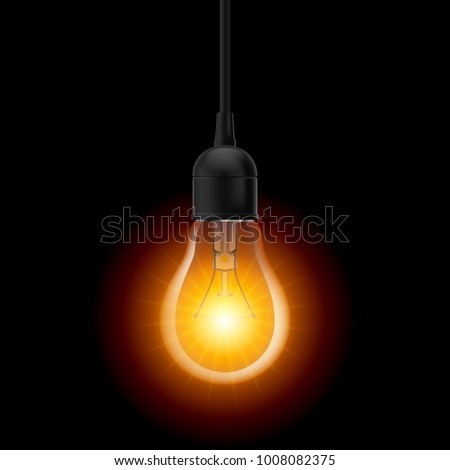 Glowing light bulb in Lamp Socket Hanging on Wire on Dark Background