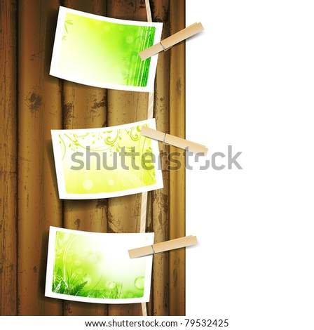 Hanging green foliage photos pinned to a Rope near wooden background over white - stock vector