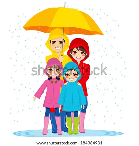 Happy family with raincoats under big umbrella on rainy day