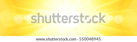 Hot glaring sun burst in a burning yellow orange sky with centered sun radiating heat, sun rays und bokeh lights in panorama format for banners or headers, footers.
