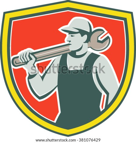 Illustration of a mechanic holding spanner on shoulder looking to the side set inside shield crest on isolated background done in retro style.  - stock vector