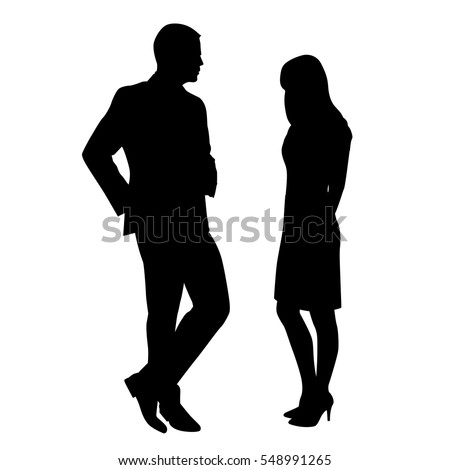 Man and woman standing and talking, flirting. The man is wearing a suit and a woman in a skirt and boots to high heels. Meeting at work or at a party