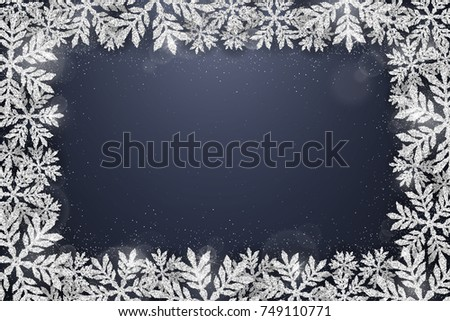 Merry Christmas and Happy New Year greeting card with silver glittering snowflakes frame on dark blue background