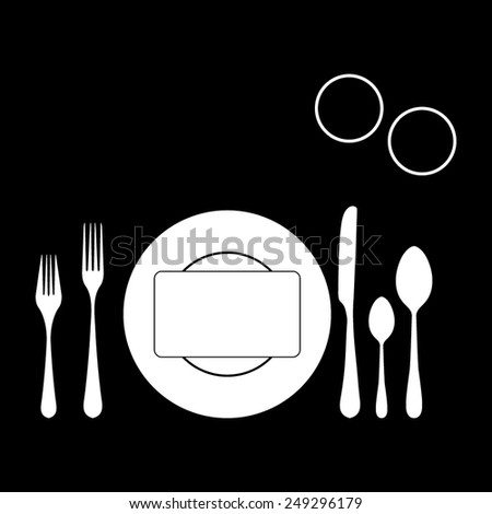 plate with spoon, knife and fork on a black background