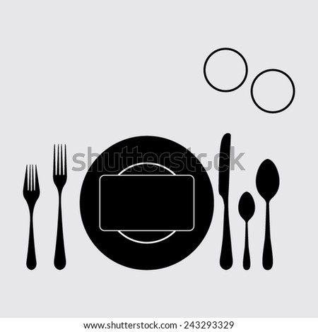 plate with spoon, knife and fork on a grey background