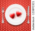 Red hearts on a plate, knife and fork. Valentine's Day - stock photo
