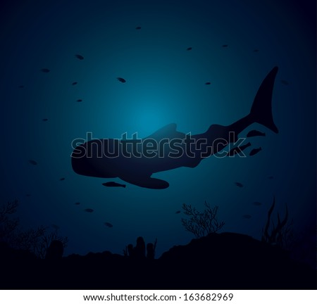 Silhouette of whale shark and coral reef in a blue sea.
