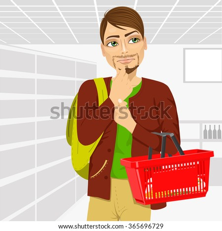 Thoughtful young man holding an empty shopping basket in supermarket