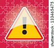 triangular warning sign on puzzle background - stock photo
