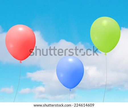Vector colorful helium balloons over a blue sky with clouds - stock vector